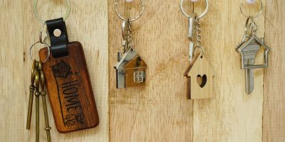House key with wooden home keyring hanging on wood board background, copy space, property concept