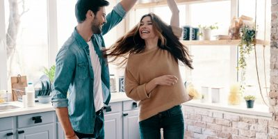 In love. Beautiful young couple in casual clothing dancing and smiling while standing in the kitchen at home
