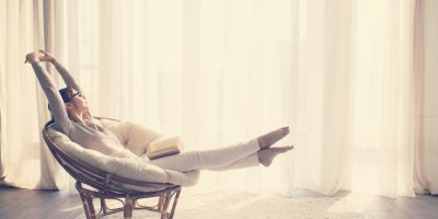 Young woman at home sitting on modern chair in front of window relaxing in her lliving room reading book